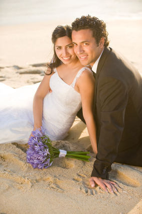 wedding bride and groom sitting on beach with bouquet