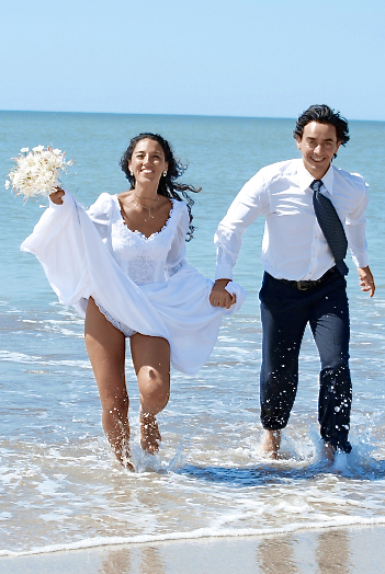 destination wedding couple running on beach
