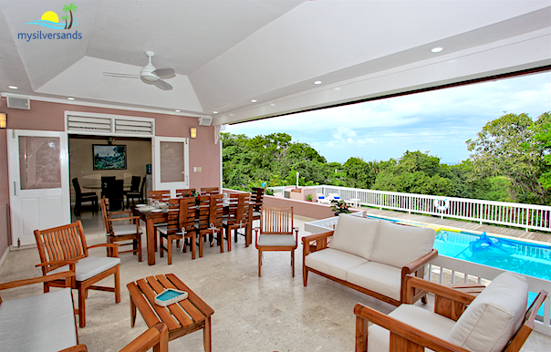 outdoor dining and lounge area overlooking the pool