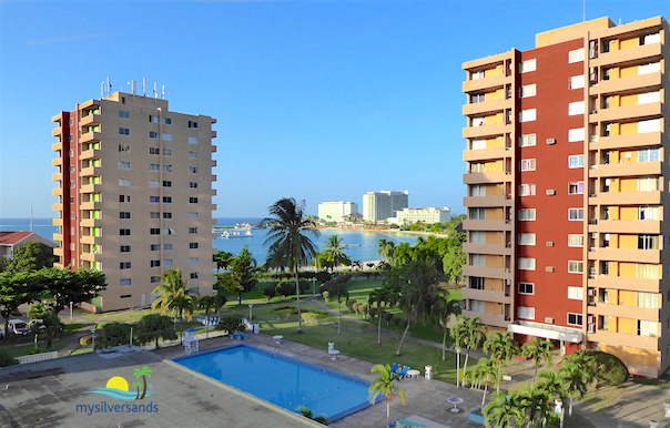 view of tower blocks, pool and sea view