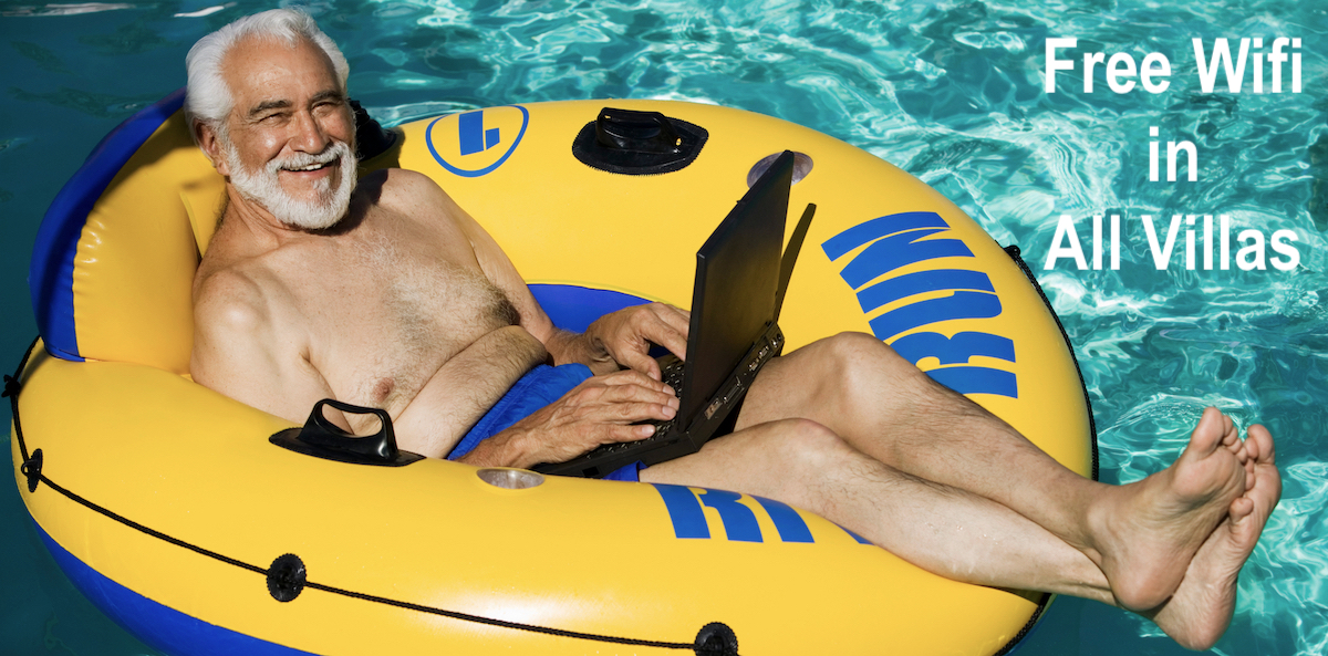 man floating in pool with laptop
