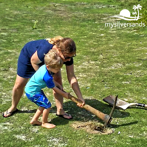 woman with boy digging hole