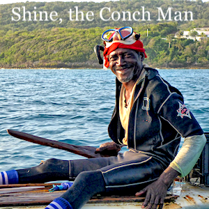 Shine, the Conch Man, sitting on his board at sea