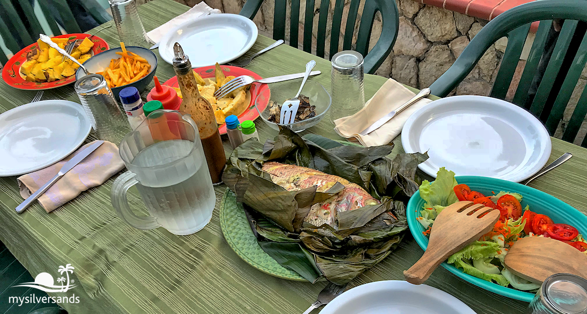 table spread with steam fish, breadfruit, sweet potato and salad