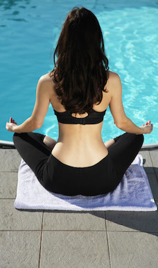 young woman sitting by pool in yoga pose