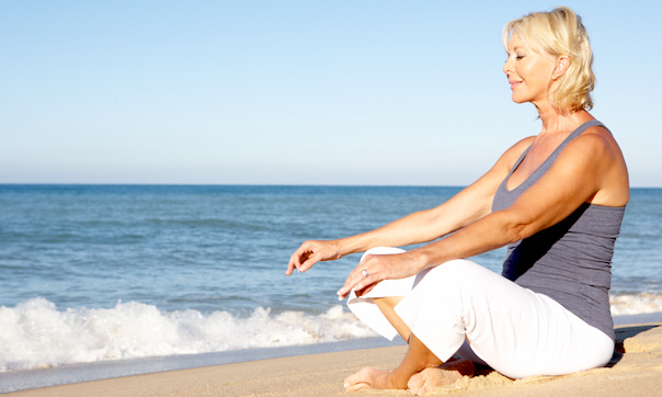 woman sitting on the beach in yoga pose