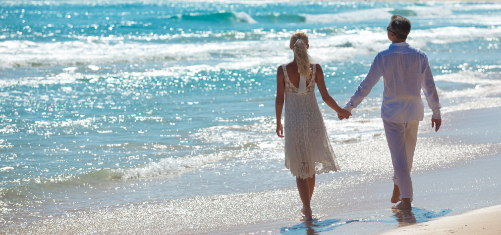 bride and groom holding hands on the beach after destination wedding