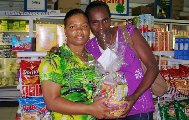 Cynthia of Tu Mac' Villa in Silver Sands Jamaica receiving her gift basket from Mavoy of Villa Mart